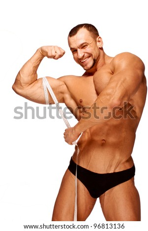 Muscular and tanned male body parts is being measured - stock photo