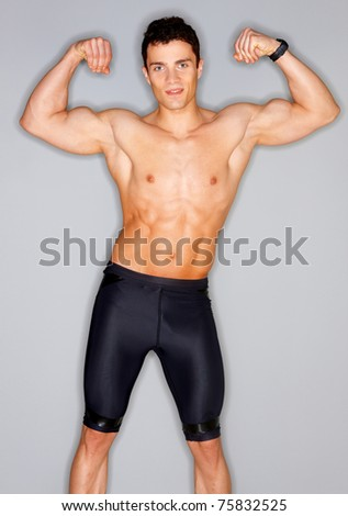 Muscular and tanned male isolated on grey - stock photo