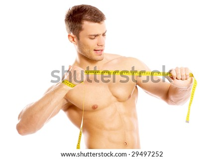 Muscular and tanned man ripping measure tape - stock photo
