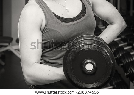 Muscular arm in the gym. Hand holding a dumbbell in suspense. Training, sports, hand, dumbbell, trainnings. - The concept of a healthy lifestyle and fitness. article about fitness and sports. - stock photo