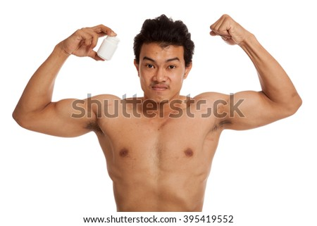 Muscular Asian man flexing biceps with white drug pill bottle   isolated on white background