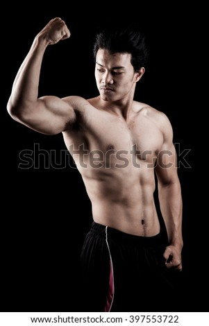 Muscular Asian man show his body on dark background - stock photo