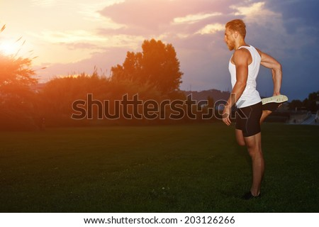 Muscular athletic runner doing stretching exercise and enjoying beautiful colorful sunset, attractive sportsman doing workout in the green park during sunset, health lifestyle and fitness concept