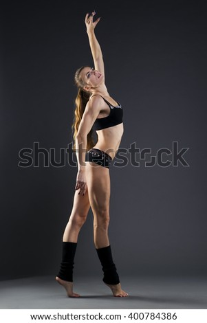Muscular attractive fitness woman on gray background in studio. Trained female body - stock photo