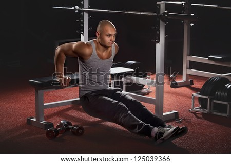 Muscular back of young bodybuilder training in fitness club - stock photo