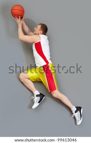 Muscular basketball player slamming the ball, overview - stock photo