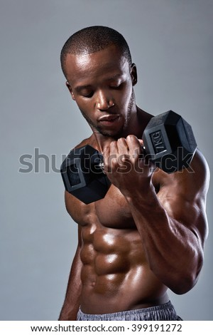 Muscular black african man with well defined muscles abs abdominal lifting weights - stock photo