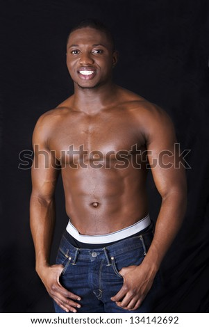 Muscular black man, against black background - stock photo