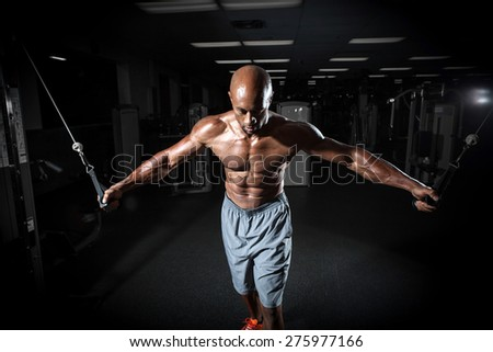Muscular body builder working out at the gym on a cable machine. - stock photo