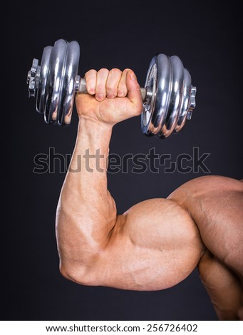 Muscular bodybuilder doing exercise with weight on dark background. - stock photo