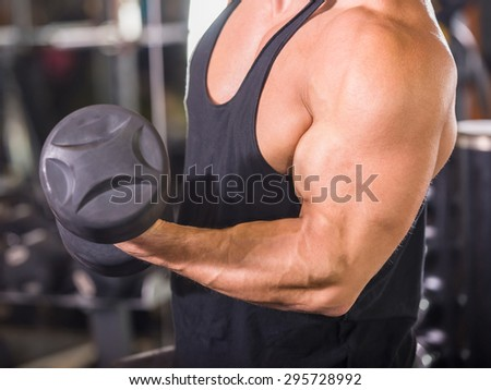 Muscular bodybuilder guy doing exercises with dumbbells at gym, close-up.