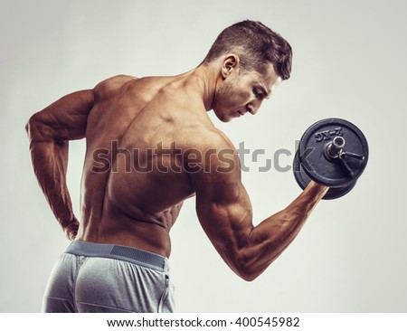 Muscular bodybuilder guy doing exercises with dumbbells over grey background with copyspace