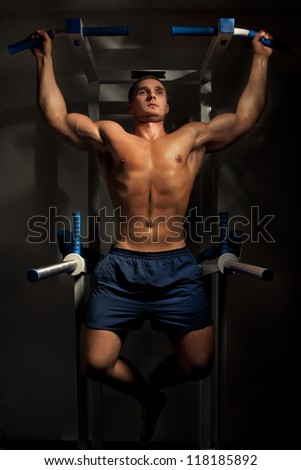 Muscular bodybuilder training in dark background - stock photo