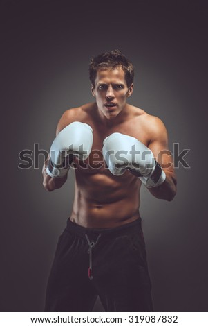 Muscular boxer in white gloves posing in studio over grey background. - stock photo