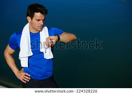 Muscular build jogger looking the time on his watch taking a break after run, athlete runner with towel on the neck resting after jogging, athlete sportsman checking the time on his wear watch - stock photo