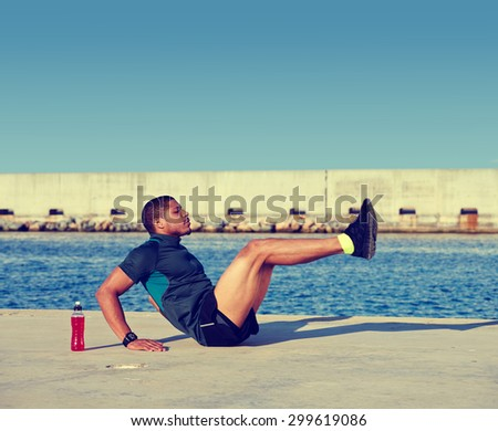 Muscular build man doing hard legs exercise before start his run at sunny afternoon outdoors,afro american sports man working out at copy space area for your text message on advertising content on top - stock photo
