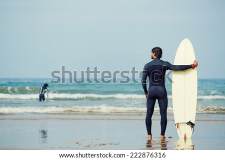 Muscular build surfer holding surfboard while standing on the beach looking at ocean to find the perfect spot to go surfing waves, professional surfer waiting waves on the ocean beach, filtered image - stock photo