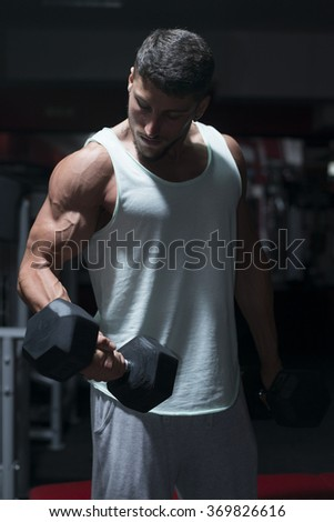 Muscular builder man training his body with dumbbell - stock photo
