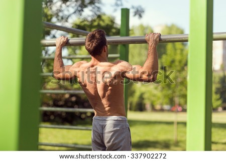Muscular built young athlete working out in an outdoor gym, doing chin-ups - stock photo