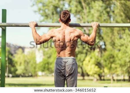 Muscular built young athlete working out in an outdoor gym, doing chin ups - stock photo
