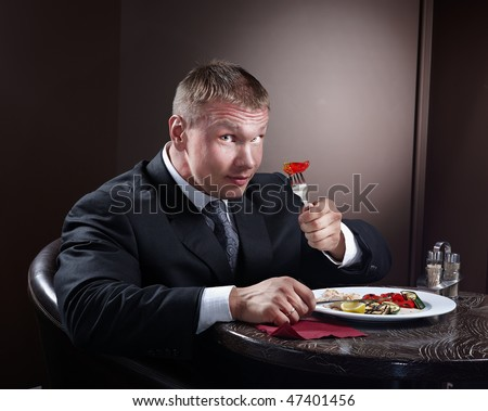 Muscular businessman eating