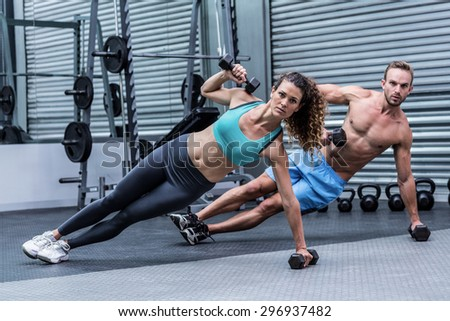 Muscular couple doing side plank while lifting weights - stock photo