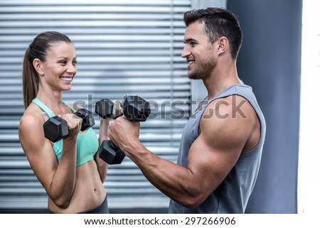 Muscular couple lifting dumbbells while facing each other - stock photo
