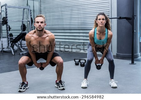 Muscular couple lifting kettlebells at the crossfit gym - stock photo