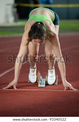 Muscular female sprinter ready to go - stock photo