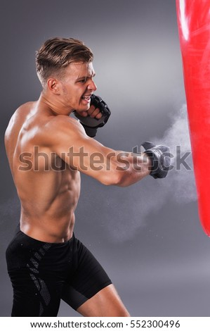 Muscular Fighter Practicing Some Kicks with Punching Bag. Boxing on Gray Background. The Concept of a Healthy Lifestyle