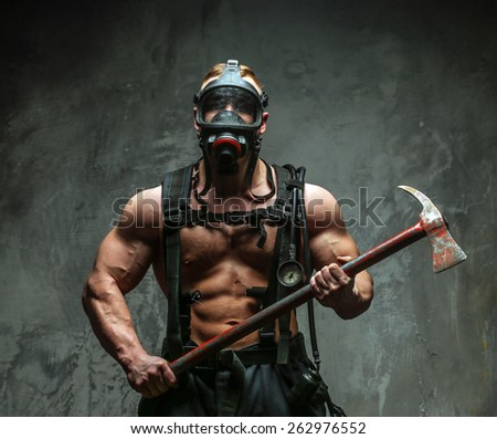Muscular firefighter with naked torso on grey background - stock photo