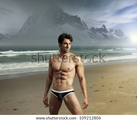 Muscular fit sexy guy on remote scenic beach location with dramatic mountains in background - stock photo