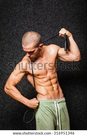 Muscular fit shirtless young man with jump rope. Young Caucasian bodybuilder in green shorts posing against black background. Medium retouch, vertical, no filter. - stock photo