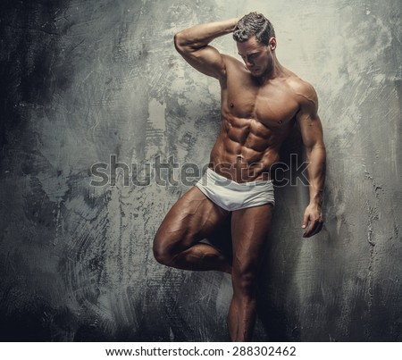 Muscular fitness model guy in white panties posing on grey background. - stock photo