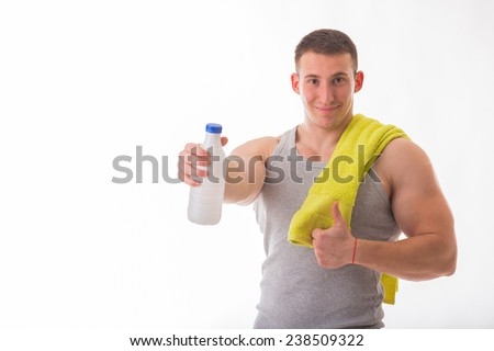Muscular guy - bodybuilder posing on white background. Athletic man holding a bottle of milk in hand, a towel around his neck. Sport, health, bodybuilding, strength, power - a concept sports. - stock photo