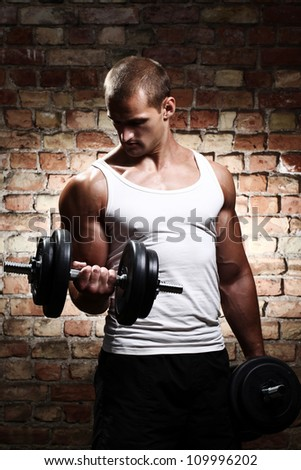 Muscular guy doing exercises with dumbbell against a brick wall - stock photo