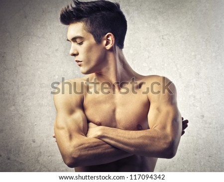 Muscular guy seeing his muscles - stock photo