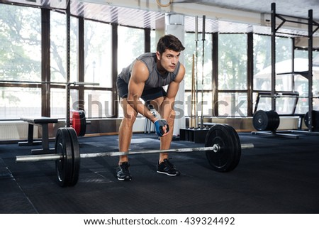 Muscular handsome man lifting barbell at gym - stock photo