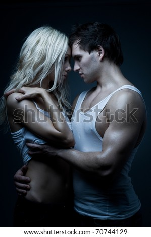 muscular handsome sexy guy with pretty woman, on dark background, glamour blue light - stock photo