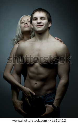 muscular handsome sexy guy with pretty woman, on dark background, glamour blue light, guy look on camera and smile - stock photo