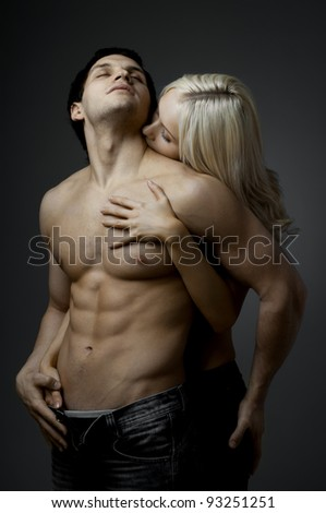 muscular handsome sexy guy with pretty woman, on dark background, glamour light - stock photo