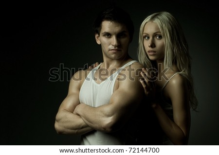 muscular handsome sexy guy with pretty woman on dark background, look on camera