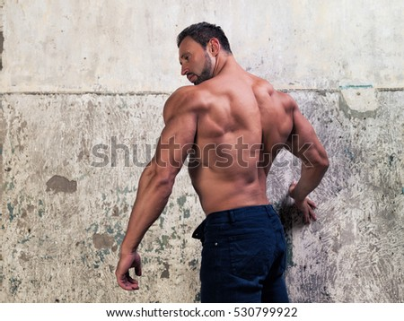 Muscular hot man poses on concrete background
