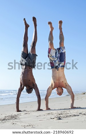 Muscular lean black man and white man perform handstand together on sandy beach under clear sunny sky - stock photo