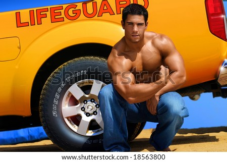 muscular lifeguard on the beach by his truck - stock photo