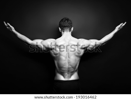 Muscular male back on black background in black and white
