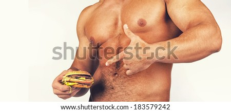 Muscular male body with tasty burger - stock photo