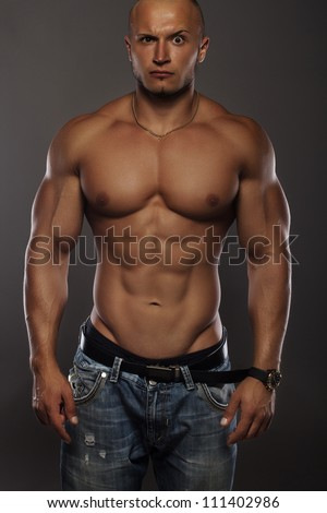 Muscular male bodybuilder on black background with a funny face - stock photo