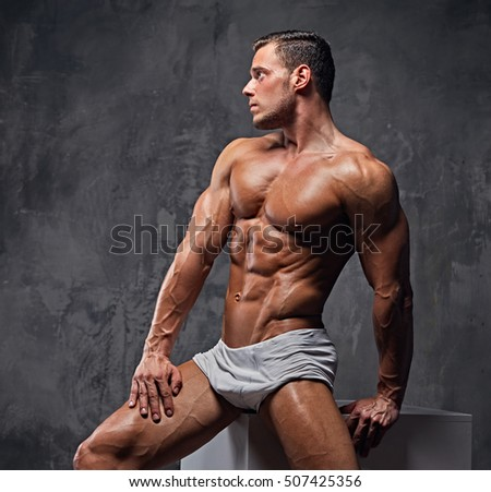 Muscular male fitness model sits on a cube in the grey wall background.