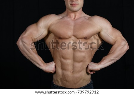 Muscular male flexing muscles, isolated on black background